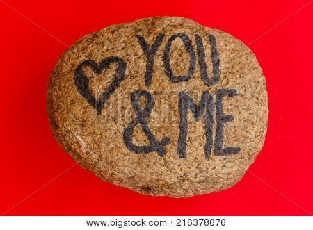 the writing you & me with a heart drawn on a stone /the writing you & me with a heart drawn on a stoneindicates the love promise of two lovers