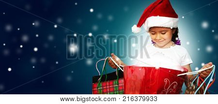 Little girl in fur-cap with shopping bags. Christmas