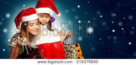 Two little girls in fur-cap with shopping bags. Christmas and magic