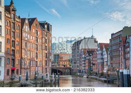 old warehouse district Speicherstadt in Hamburg Germany under clear summer sky as seen from Zollkanal channel with with Sankt Katherinen church and Elbphilharmonie in background