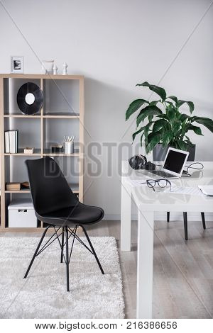 Cozy office for a real music lover. Laptop and headphones on table near chair. Retro music record plate is on shelf
