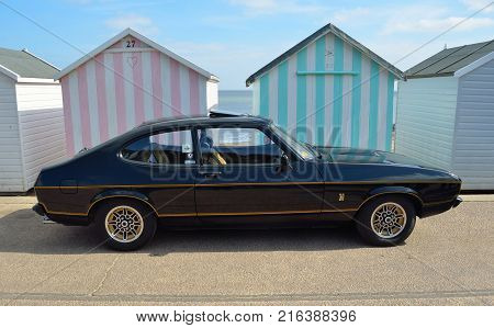 FELIXSTOWE, SUFFOLK, ENGLAND -  MAY 07, 2017:  Classic Black Ford Capri  3.0 Litre Motor Car Parked on seafront promenade in front of beach huts.