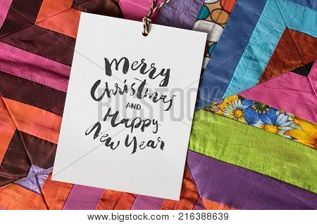 crafting, present, new year concept. close up of handmade blanket, created of different textile pieces of wonderful bright coloures, green, blue, pink and orange and white greeting card