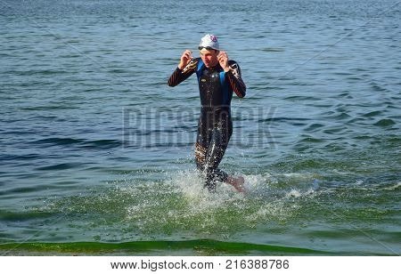 GRAFHAM, CAMBRIDGESHIRE, ENGLAND - AUGUST 06, 2017:  Leading Competitor  Leaving the water at the end of the swim.