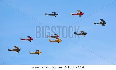 OLD WARDEN, BEDFORDSHIRE, ENGLAND - AUGUST 06, 2017:  Nine Tiger Moth Vintage Bi Planes Flying.
