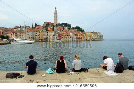 ROVINJ, ISTRIA, CROATIA - JUNE 15, 2017:   Students  sitting on quay drawing old town of Rovinj.