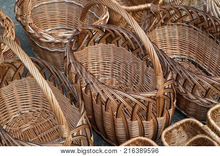 Several rows of wicker baskets. Basket woven of twigs. Patterns of waves and braids. Baskets with handles of different shapes. Basket for fruit or fungi or for a hike in the store.