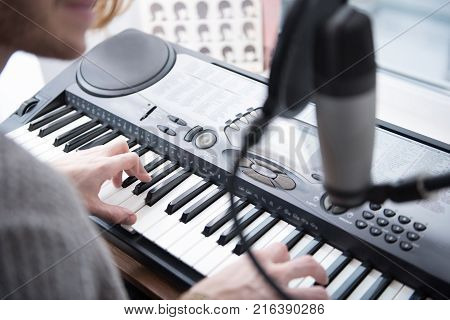 Close up of arms of young pianist performing music on synthesizer