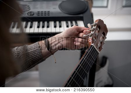 Close up of guitarist hands tuning his musical instrument in studio