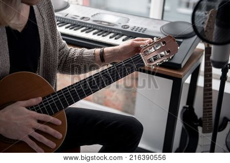Close up of arm of young woman fixing strings of guitar while twisting pads. He is sitting near synthesizer and microphone