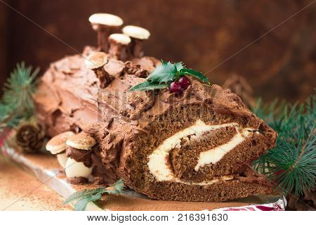 Traditional Christmas dessert Christmas yule log cake with chocolate cream cranberry and rosemary twigs. On a dark background with Christmas tree branches gifts and decorations copy space