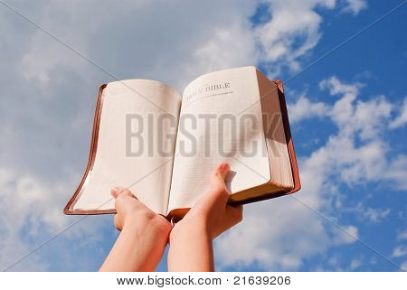 Hands Hold The Open Bible Against Blue Sky