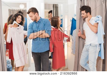 Men in the fitting room are waiting for their girls. Girls trying on things in the fitting room. Young people try on clothes in fitting room.