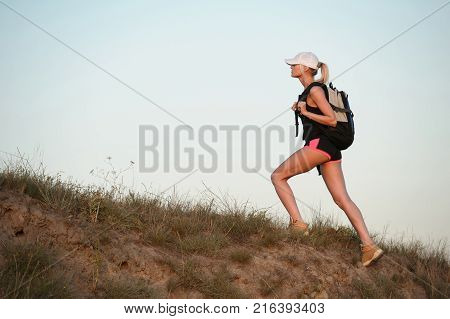 Young woman tourist with backpack goes up the hill and looking on top of the hill. Blue sky background