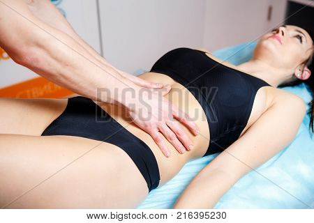 The Hands Of A Masseur Make A Relaxing Massage To A Woman On The Abdominal Abdomen For Toning The Mu
