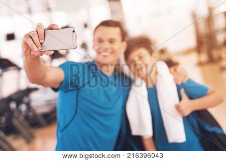 Father with his son in the same clothes in the gym. Father and son spend time together and lead a healthy lifestyle. A man and a boy make selfie at the gym. They have on their necks bath towels