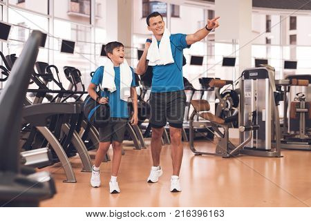 Father with his son in the same clothes in the gym. Father and son spend time together and lead a healthy lifestyle. The man is showing the gym to the boy. The boy is delighted with the gym.