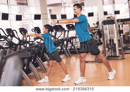Father with his son in the same clothes in the gym. Father and son spend time together and lead a healthy lifestyle. A man with a boy does a warm-up before training.