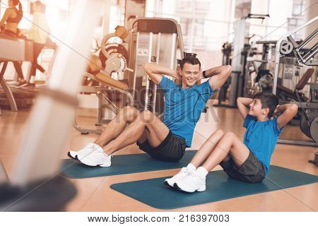 Father with his son in the same clothes in the gym. Father and son spend time together and lead a healthy lifestyle. Man and boy are pump the abdominals.