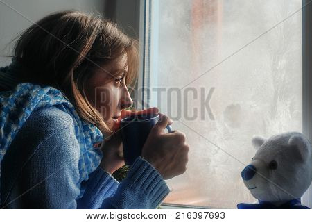 Sad upset lonly beautiful young woman with the cup in sweater dreaming near the frozen window at home