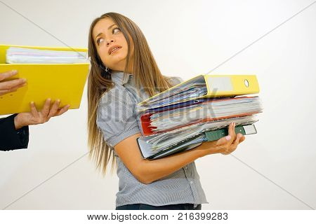 The boss gives pack of documents to busy manager. Boss give extra work to executor. Office worker receiving a lot of paper work. Woman in depression with a big pile of files to work.