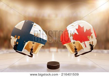 Low angle view of hockey helmets with Canada and Finland flags painted and hockey puck on ice in brightly lit stadium background. Concept of intense rivalry between the two hockey nations.
