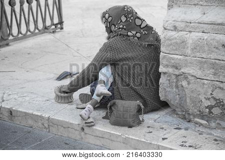 Beggar with a child in her arms in front of the entrance of a church