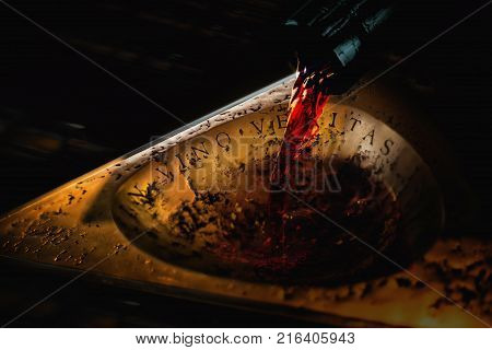 Dark bottle neck with red running wine to an ancient golden plate with the inscription IN VINO VERITAS. Close up
