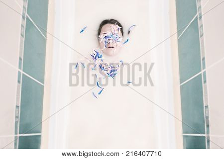 portrait of a girl in a tub of milk with flower petals on the eyes