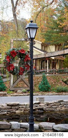 Christmas wreath hanging on rustic old light pole