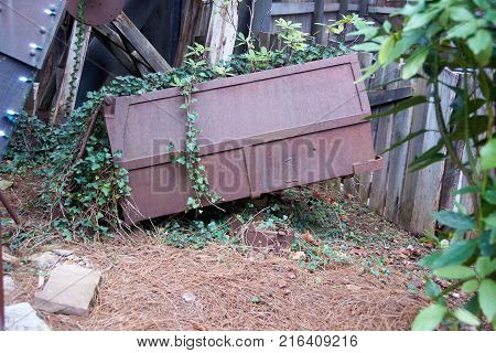 Large rusty old mine car laying on ground
