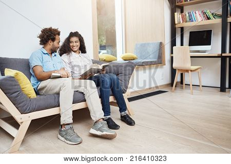 Pair of two dark-skinned multi ethnic people on a date in library. Couple sitting on sofa, reading favourite books, laughing, spending comfy time together.