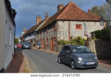 ALFRISTON, EAST SUSSEX, ENGLAND  -  OCTOBER  22, 2017:  Cars  being driven through  the narrow  streets  of picturesque  Alfriston East Sussex.