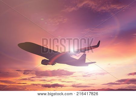 Silhouette Of Windmills For Electric Power Production And Airplane Take Off On The Colorful Dramatic