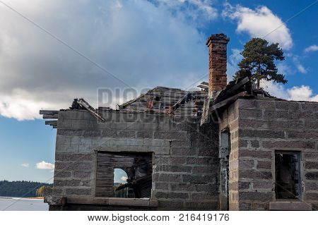 Ruins of an abandoned old house with rock walls and wooden roof in ruins near Shiroka Polyana lake in Bulgaria during sunny winter day with white clouds.