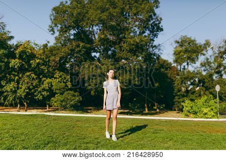 Young pretty girl with long brown hair dressed in light clothes staying on green lawn grass in the park on trees background. Summer sunny time