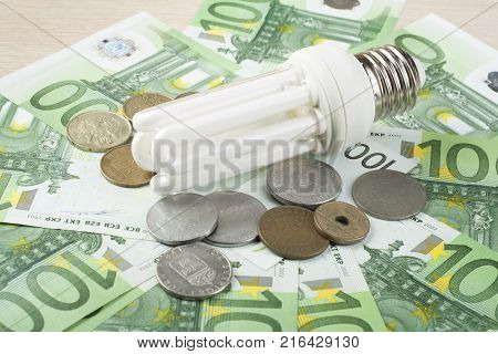 Energy saving fluorescent lamp on money background, Eco energy saving light bulb, comparison of energy saving lamps and incandescent lamps.