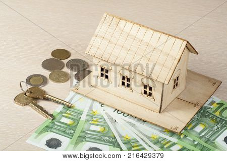 Model house, keys and money on wooden office desk table.Financial and property concept.