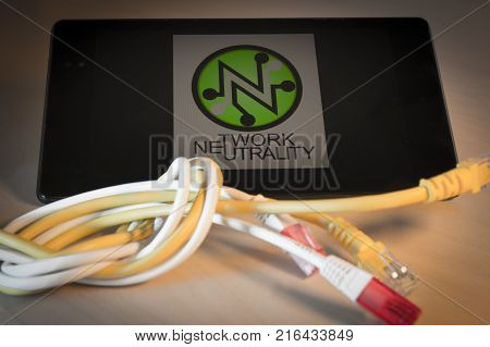 knotted net cable over a smartphone with the words and the icon of Net Neutrality on screen. Suitable for concepts as net neutrality regulations, Internet Freedom Preservation Act , Open Internet order.