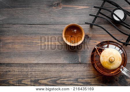 Tea break. Cookware fo tea ceremony. Tea pot and cups on dark wooden background top view.