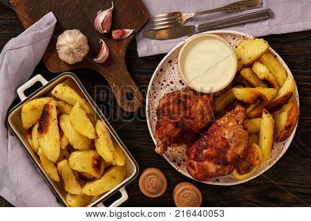 Roasted turkey knuckles with baked potatoes on wooden background.
