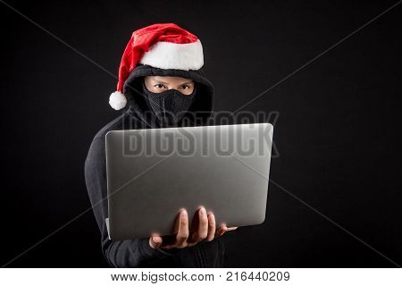 Mysterious male santa hacker holding laptop computer anonymous man on black background ransomware cyber attack and internet security on Christmas holiday concepts