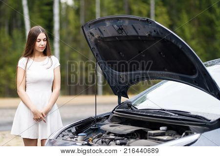 woman near broken car looking under opened hood