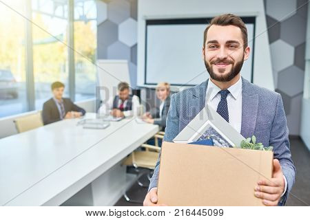 Waist-up portrait of handsome bearded manager in classical suit looking away with wide smile while holding cardboard box with belongings in hands, interior of spacious boardroom on background