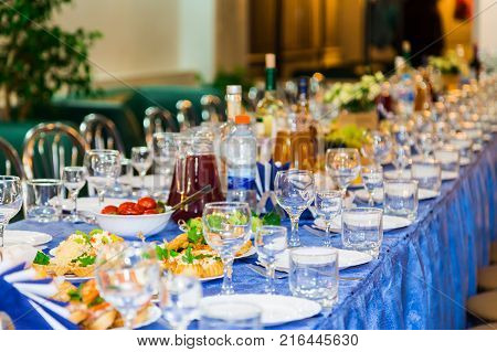 Served tables at the Banquet. Drink, alcohol, delicacies and snacks. Catering. A reception event.