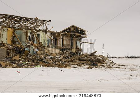 Old two-storied destroyed, ruined and desolated house in winter with snow around. Poverty and misery, North