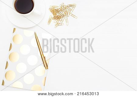 Coffee break. Desktop with gold stationery and coffee