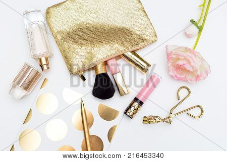 Cosmetics for make-up of gold color on a white background. Flat lay