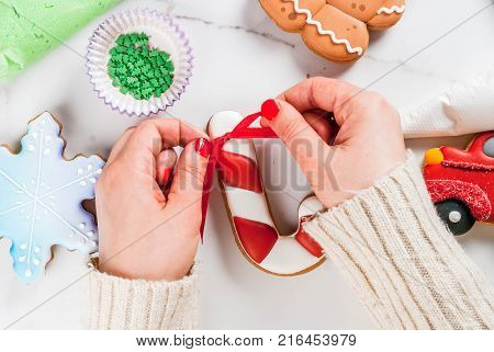Preparing for Christmas decorating traditional gingerbread with multicolored sugar icing white marble table. Girl (hands in picture) knot ribbon bow on candy cane gingerbread top view copy space