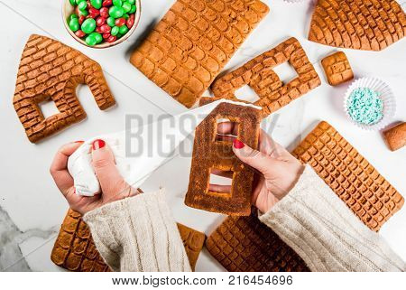 Preparation for Christmas New Year. Cooking and decoration of traditional advent gingerbread house female hands in picture top view white marble background.